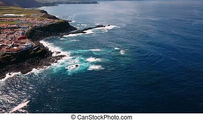 Flying over the ocean surf on the reefs coast in Maia city of San Miguel island, Azores, Portugal.