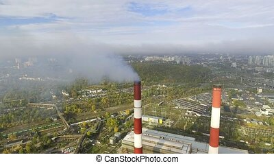 flying over the pipes of the plant from which the smoke goes