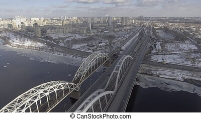 Flying over the railway bridge and trasskoy near residential area, people go to work in the office, on the street winter