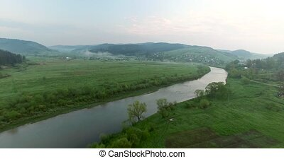 Flying over the river in a hilly valley. Aerial view