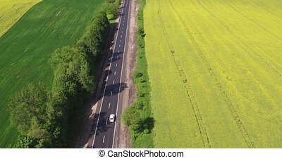 Flying Over the Road Trafic in a Field - Aerial view Car...