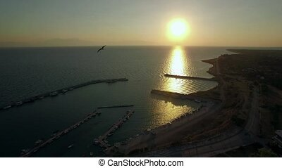 Flying over the sea and quay at sunrise, Greece