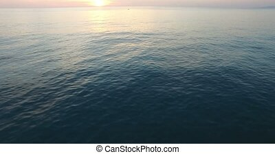 Flying over the sea in the sunset and two boats.