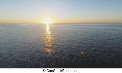 Flying over the sea towards rising sun - Aerial footage...