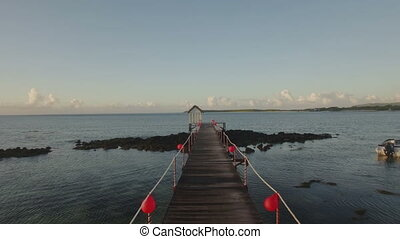 Flying over the wooden pier in water