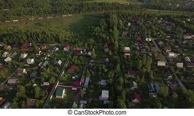 Flying over village houses and moving cargo train - Aerial...