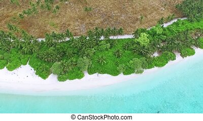 Flying over water, stone and sand beach in the Maldives...