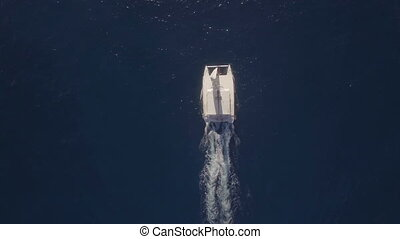 Flying over white yacht sailing in blue ocean
