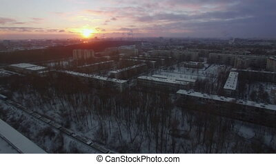 Flying over winter city and moving cargo train. St. Petersburg scene at sunrise