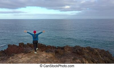 Flying over woman in sportswear stands on top of a rock with...