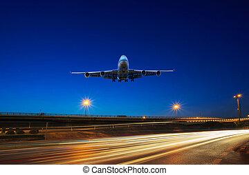 flying passenger jet plane above traffic light on express...