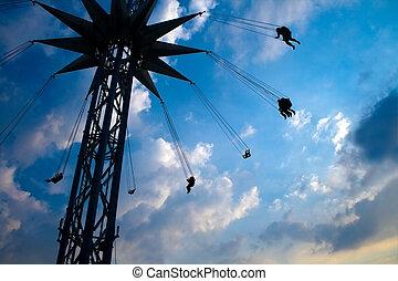 Flying people on swinging carousel
