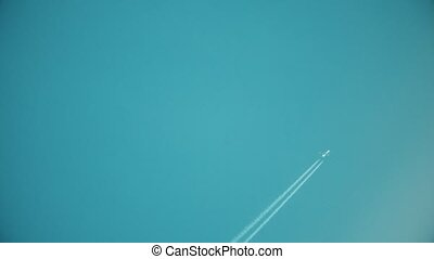 Flying plane leaving contrain in the blue sky.