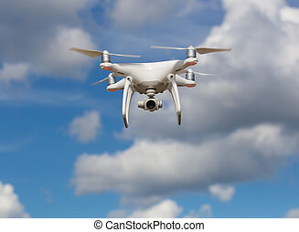 flying quadcopter in blue sky - flying quadcopter with ...
