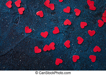 Flying red paper hearts on dark blue background. Valentine's Day.