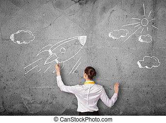Flying rocket - Rear view of businesswoman drawing rocket on...