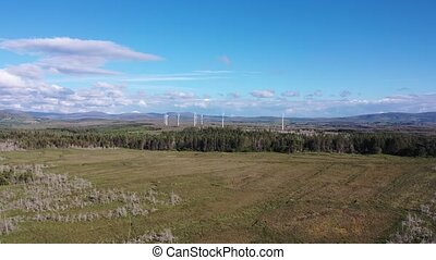 Flying towards the wind power turbines on a peat bog between...