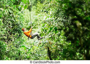 Adult Tourist On Zip Line Dressed In Orange Against Green Background