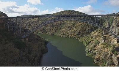 Flying under iron bridge over river - Pino Bridge en Zamora,...