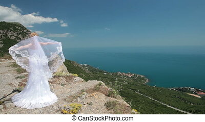 flying veil - bride stands on cliff with a flowing veil on...