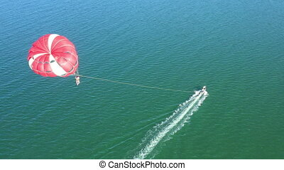 Flying with Parachute Behind a Boat. Drone view.