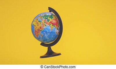 Flying zero gravity globe on yellow background. School class of geography. Ecology concept. Earth day. High quality 4k footage