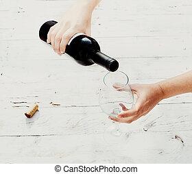 flytande röd vin, från, flaska, in, tom, wineexponeringsglas, vita, trä, bakgrund, med, copyspace., hålla lämna, a, flaska vin