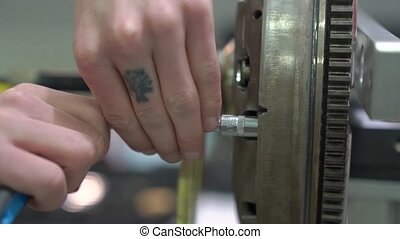 Flywheel car engine mechanic hands repairs at service station internal parts of machine vehicle motor camera movement