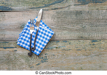 Fnife, fork and napkin are on wooden background
