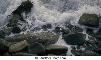 Foam and bubbles from the wave on the stones slow motion -...