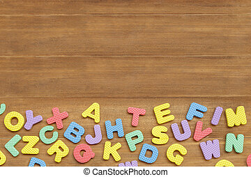 foam english alphabet letters on wooden background