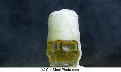foam flows out of the glass of pilsener or lager beer in...
