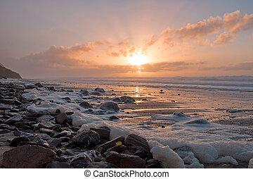 Foam on the rocks at the atlantic ocean at sunset