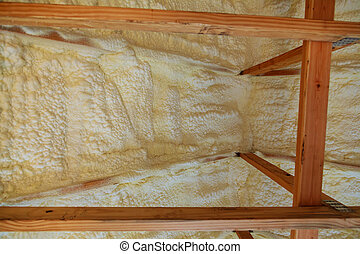 Foam plastic insulation installed in the sloping ceiling of a new frame house.