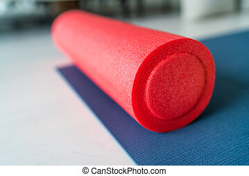 Foam roller fitness equipment on exercise mat gym floor. Indoors closeup of sports object, accessory for athletes to massage tired and tense muscles.