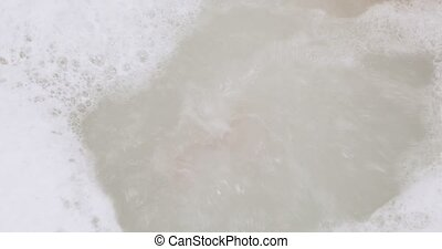 Foam soap in the bathtub - In the bathtub water boiling and...