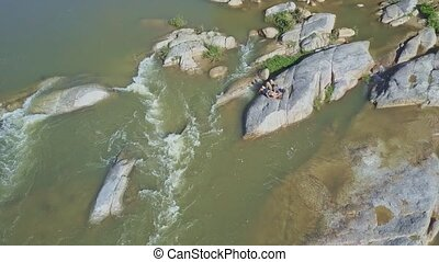 Foamy Rapids and Couple on Boulder Control Drone against...
