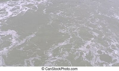 Foamy sea surface and sandy beach fly by video