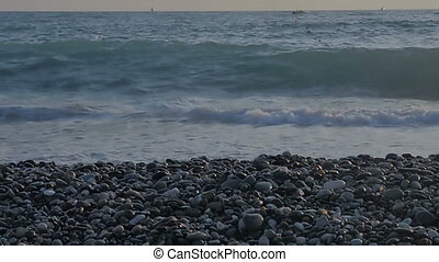 Foamy sea waves and a pebble beach.