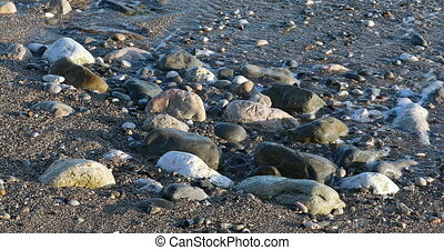 Foamy Sea Waves On Sand Beach And Stones