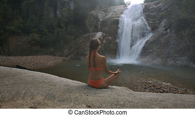 Foamy Waterfall Runs among Rocks Girl Sits in Yoga Pose