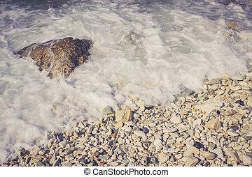 Foamy wave hits pebble rocks on the beach