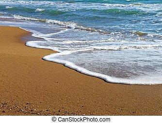 foamy wave of the sea splashing on a sandy beach