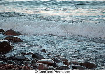 Foamy wave on the stone seashore