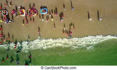 foamy waves roll on beach children gambol - drone upper view...