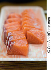 Focus and close up to Sashimi Salmon in Foam plate on the wood table.