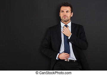 Focus businessman wearing tie against blackboard