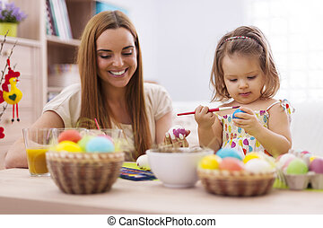 Focus little girl painting easter eggs with her mother