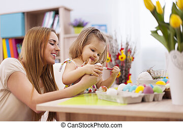 Focus little girl painting easter eggs with mother