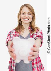 Focus of a woman holding a piggy bank